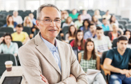 stock-photo-38640558-smiling-professor-in-the-classroom.jpg